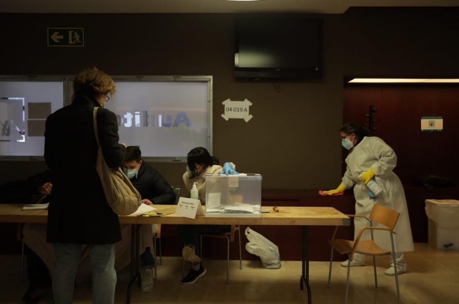 Una mujer desinfecta una mesa en un colegio electoral de Barcelona.