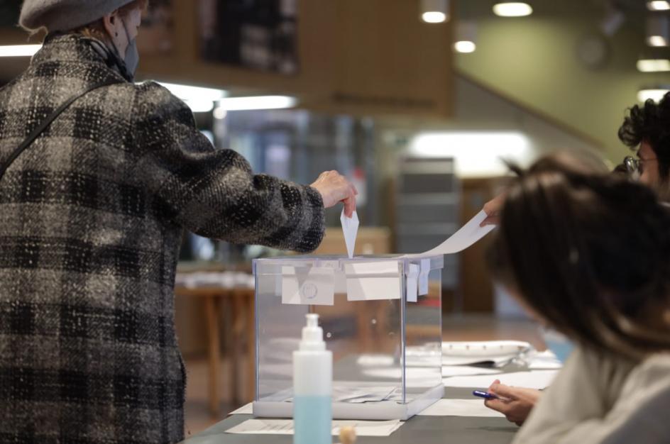 Una mujer deposita su voto en una urna en en un colegio electoral de Barcelona.
