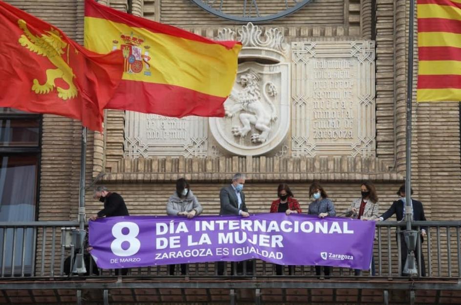 La corporación municipal coloca una pancarta en el balcón del Ayuntamiento de Zaragoza, con motivo del 8-M.