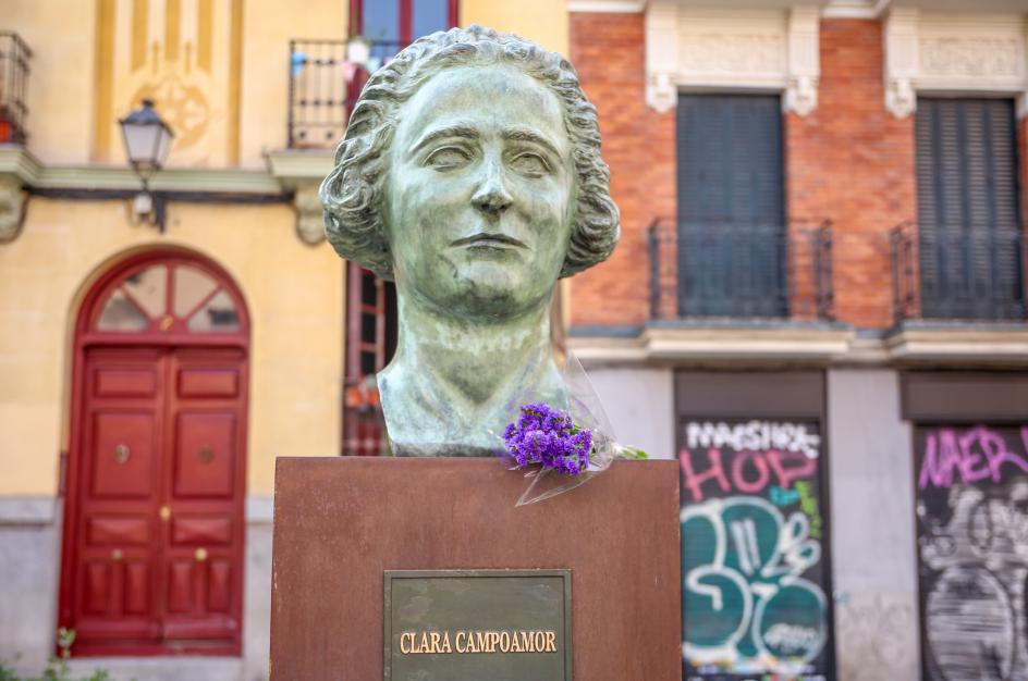 La estatua de Clara Campoamor, junto a un ramo de flores moradas, durante un acto del Movimiento Feminista de Madrid a favor de la abolición de la prostitución, con motivo del 8-M.