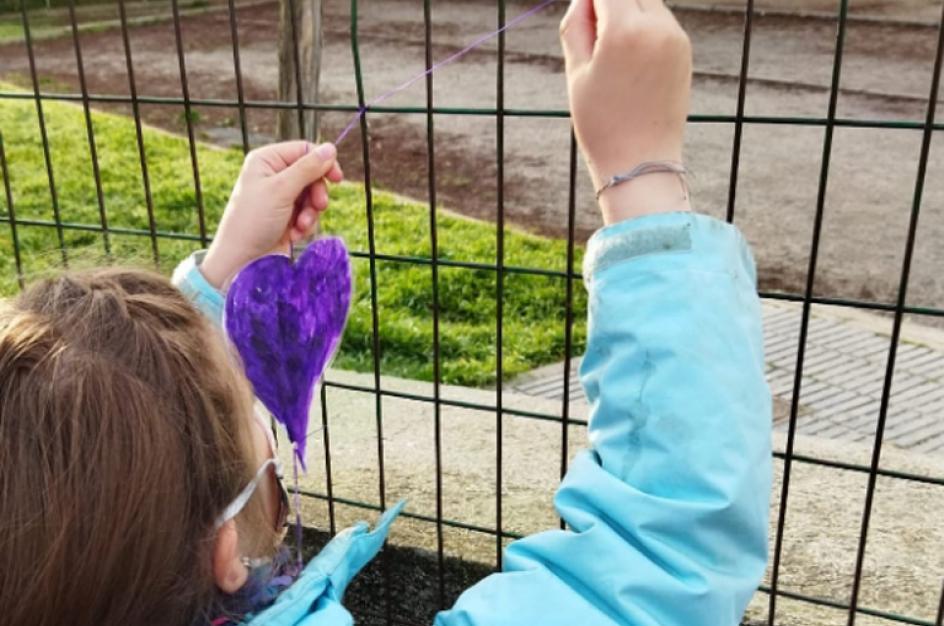 Una niña coloca un corazón violeta en la verja de su colegio, durante la celebración del 8-M en Madrid.