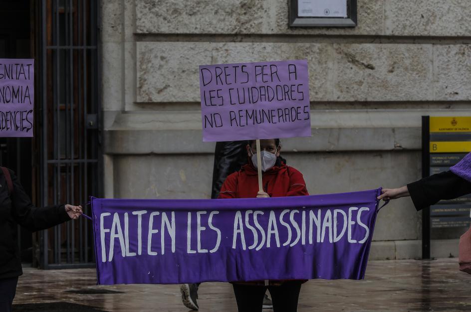 """Una participante, en una concentración por el 8-M en Valencia, sostiene un cartel donde se puede leer: """"Falten les Assessinades"""" (Faltan las asesinadas)."""