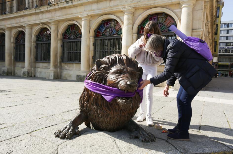 Una 'performance', realizada en León con motivo del 8-M, cubre una escultura con una banda violeta, color con el que se identifica el Día Internacional de la Mujer.