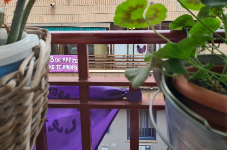"""Un balcón de una edificio en Madrid decorado con una pancarta que dice: """"8 de marzo, no te rindas""""."""