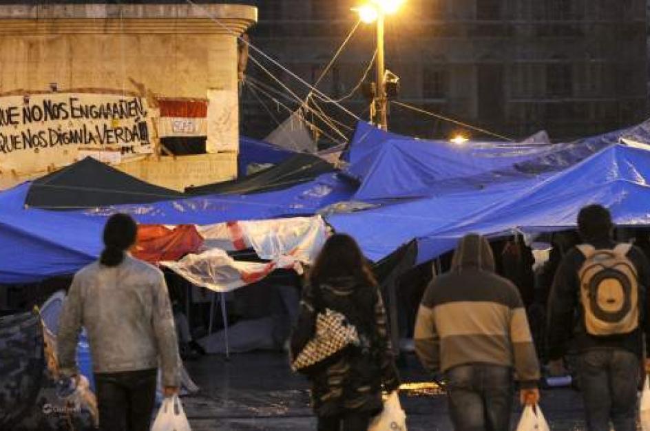 Miles de personas pasan la noche en tiendas de campaña tras un día de protestas bajo la lluvia.