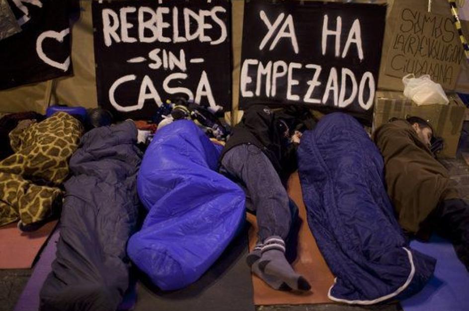 Varias personas pasando la noche en sacos de dormir en la Puerta del Sol de Madrid.