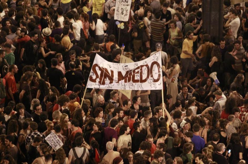 Integrantes de la manifestación alzan un cartel donde se lee 'sin miedo', una de las frases identificativas del Movimiento 15-M.