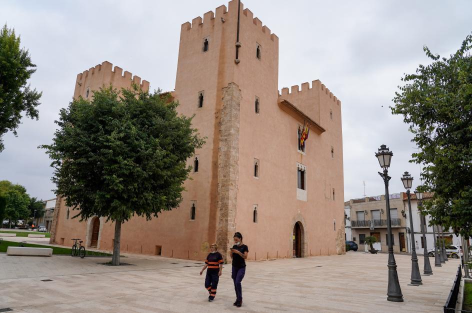 Una mujer camina sin mascarilla junto al castillo.