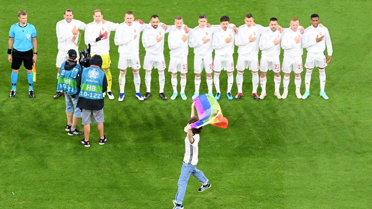 Un espontáneo salta al césped del Allianz con la bandera arcoíris durante el himno de Hungría